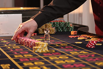 croupier with fiche on a roulette table.